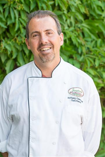 Man in a chef's apron smiling and posing for photo