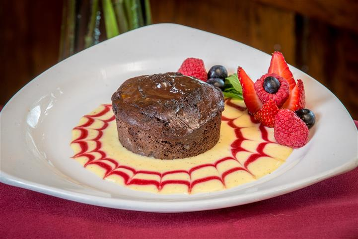 Chocolate lava cake with cream decorated with strwberries and other fruit