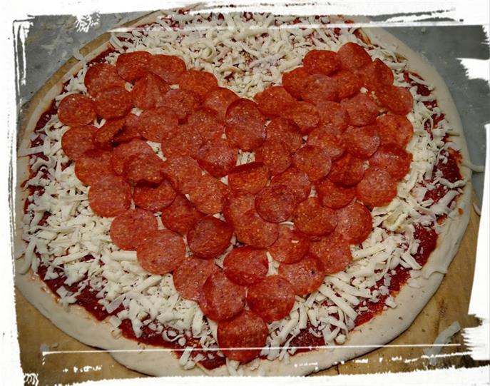 Unbaked Pepperoni pizza with pepperonis in a heart shape