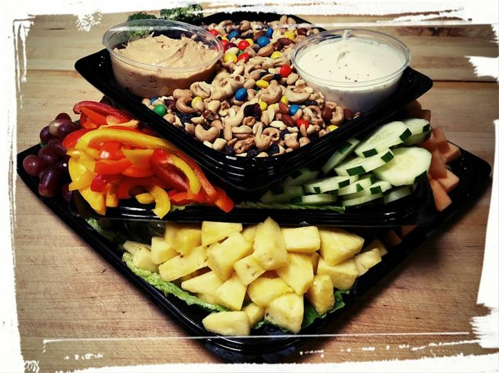 Assortment of Cucumbers, Sliced peppers, Pineapples, hummus, ranch sauce, nuts, and m&m's