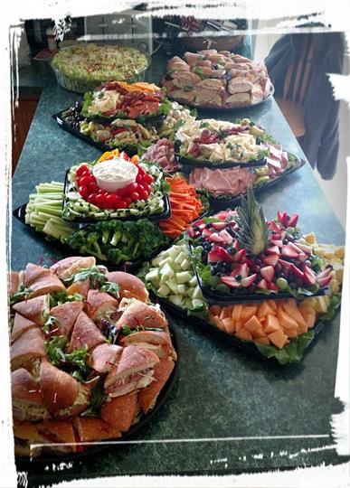 Assortment of multiple platters of Sandwiches, Fruits, Vegestables, and meats