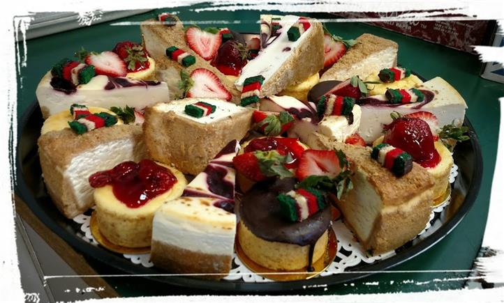 Assortment of cheese cake and fruit tarts topped with strawberries and icing
