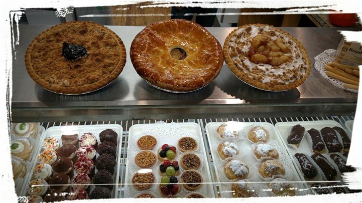 Baked pies on a display with an addition of cupcakes, cookies and chef specialty pastries