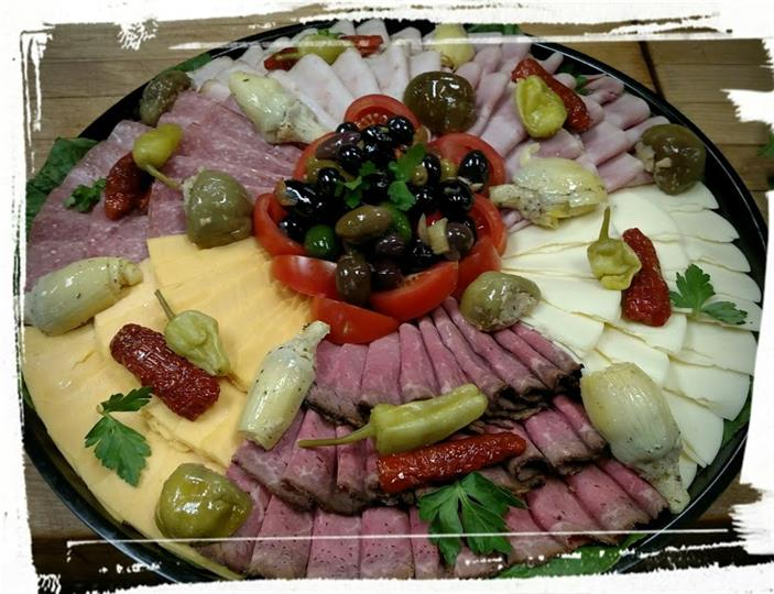 Assortment of Ham, turkey, cheese, peppers, olives, and tomatoes