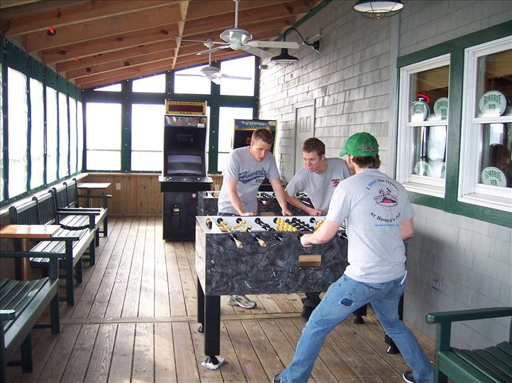 Young men playing foosball in gaming area in front of arcade games.