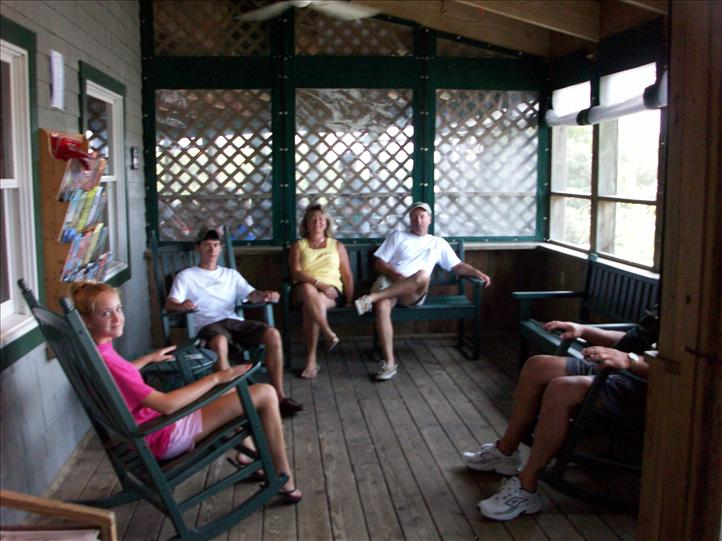 Family sits on chairs in patio area