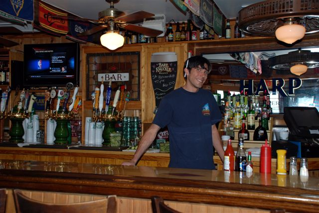 Bartender behind bar.