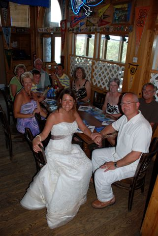Bride with family sitting at table on patio.