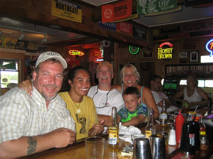 Family smiling for photo in bar area.