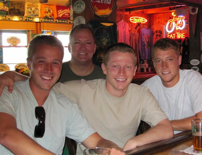 Men at bar smiling for photograph
