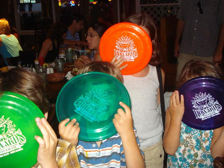 Children holding up Howard's Pub frisbees inside restaurant
