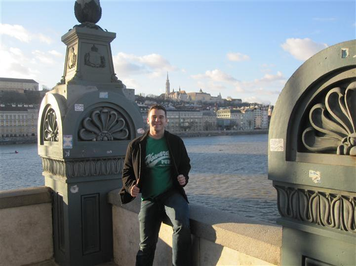 Man wearing Howard's Pub t-shirt sitting on bridge ledge looking over the Danube River in Budapest