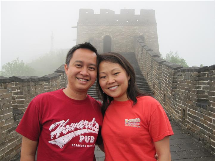 Man and woman wearing Howard's Pub t-shirts on great wall of China.