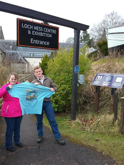 Man and woman holding Howard's Pub t-shirt in front of Loch Ness Centre entrance.