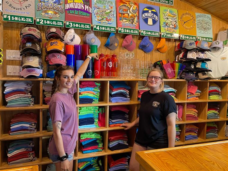 Retail shop showing hats, t-shirts, mugs, and waterbottles, with two employees in front