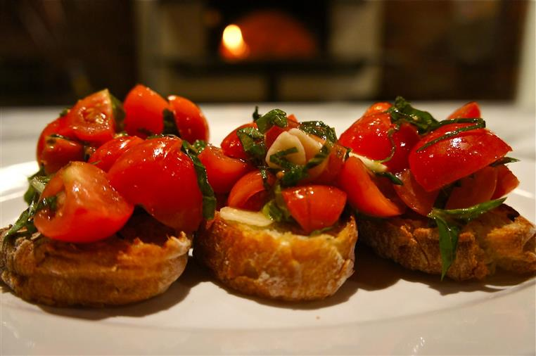 tomato and basil on top of small slices of bread