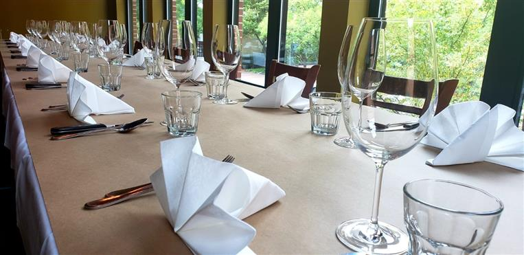 empty wine glasses on a table with folded napkins and utensils