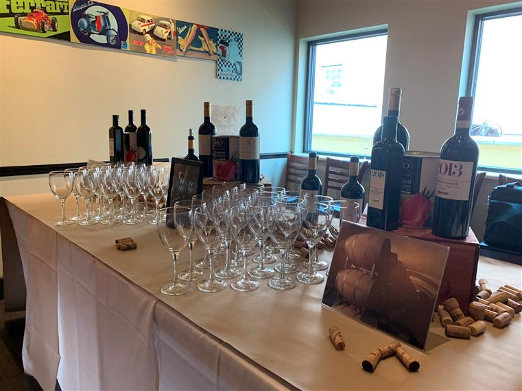 table with empty wine glasses with bottles of wine, wine corks, and pictures being displayed