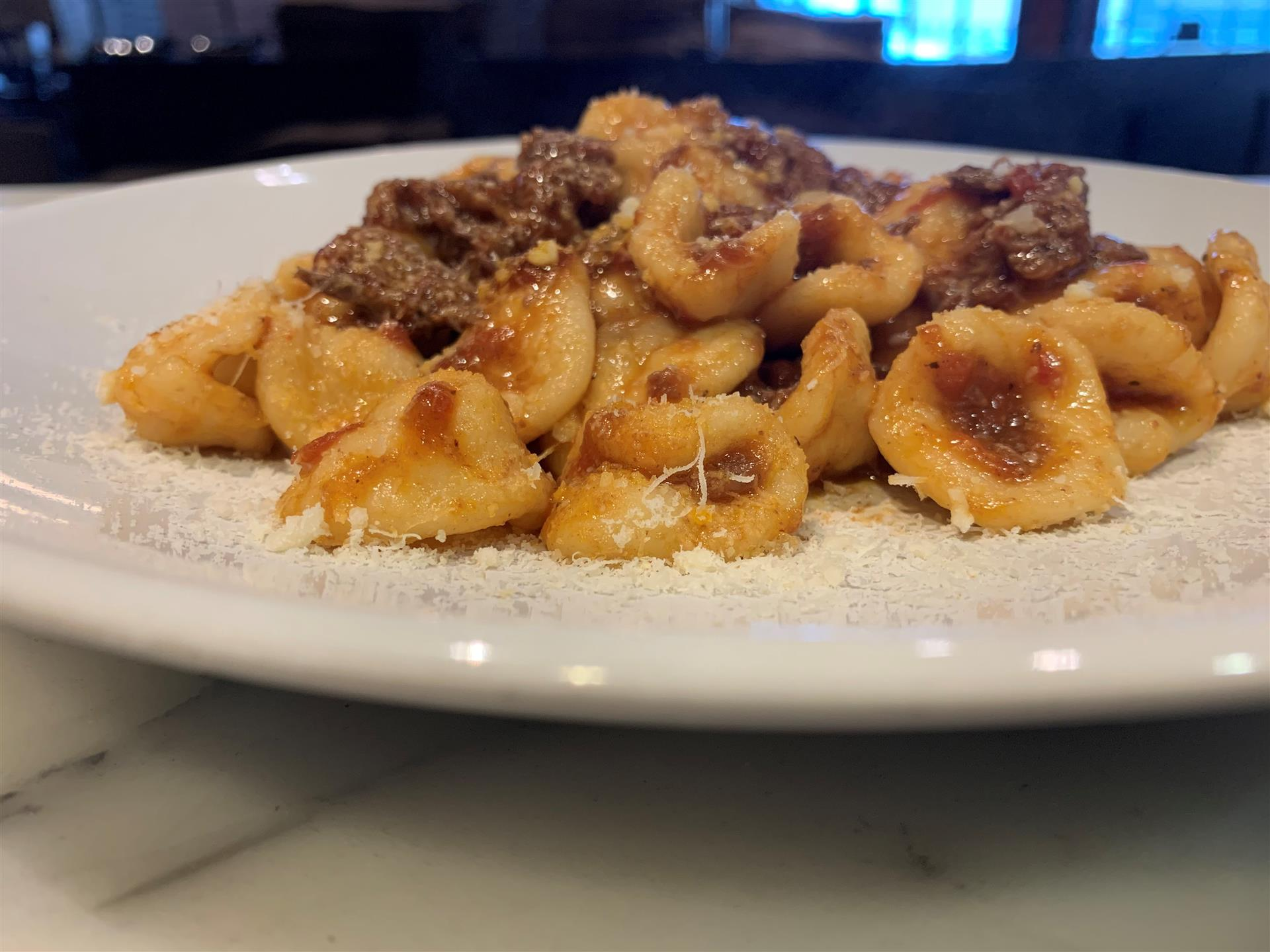 Homemade Orecchiette pasta with Short Rib Ragù on a plate and topped with cheese