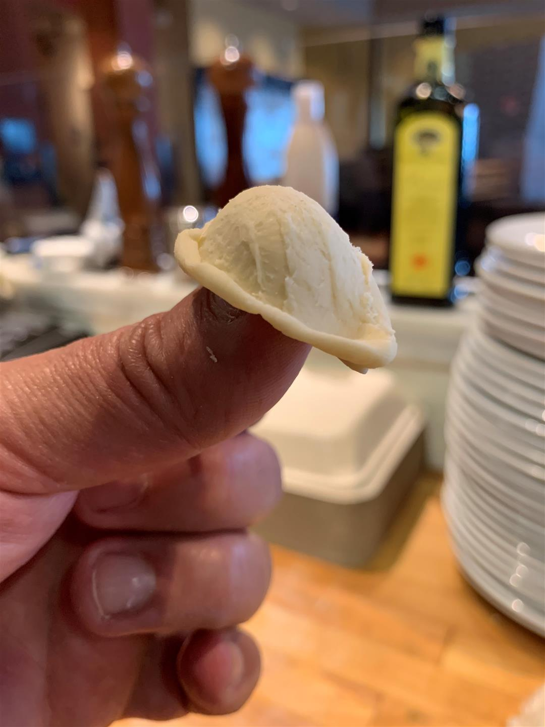 Close up of someone holding a piece of homemade and shaped orecchiette pasta