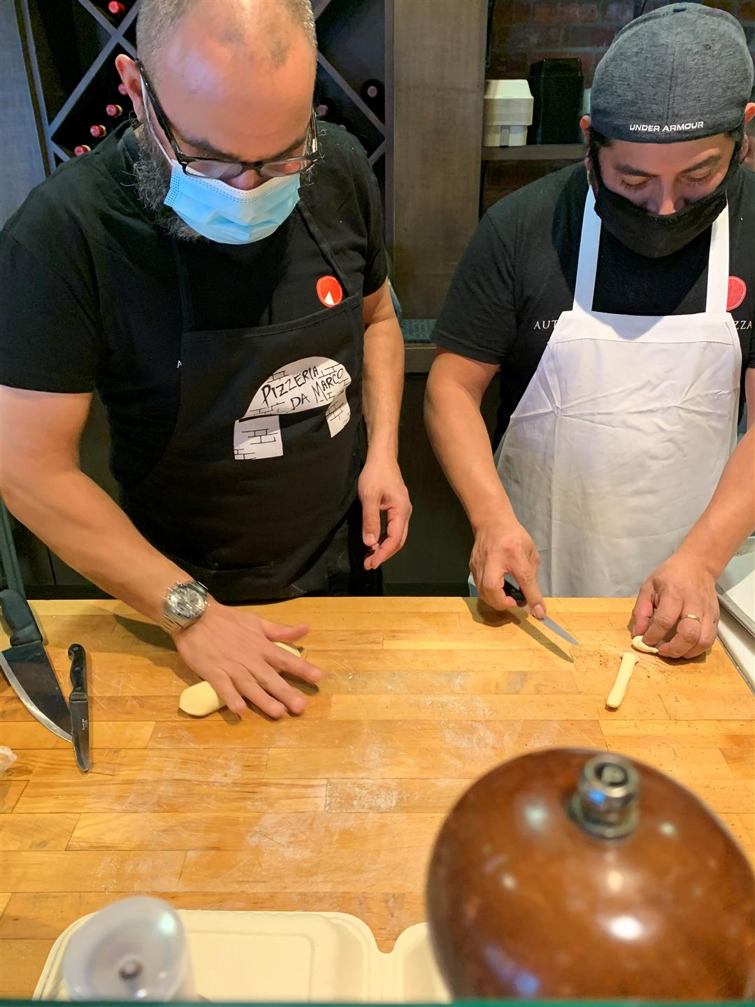 Two people rolling and shaping homemade pasta