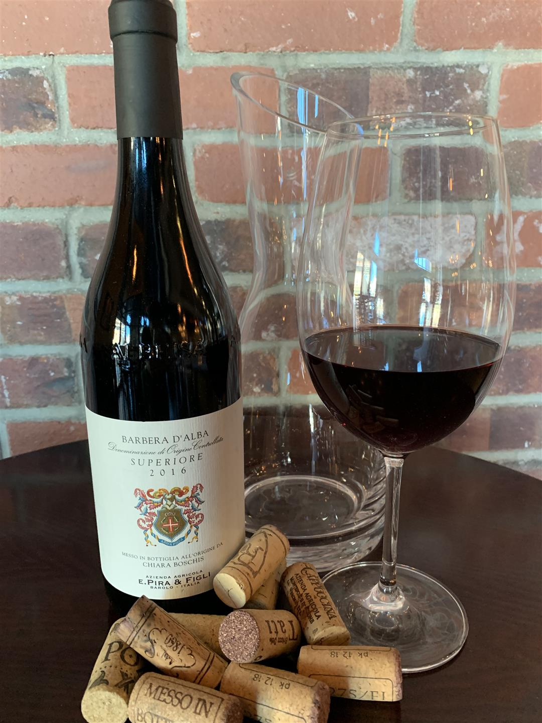 bottle of red wine with glass of wine and several corks