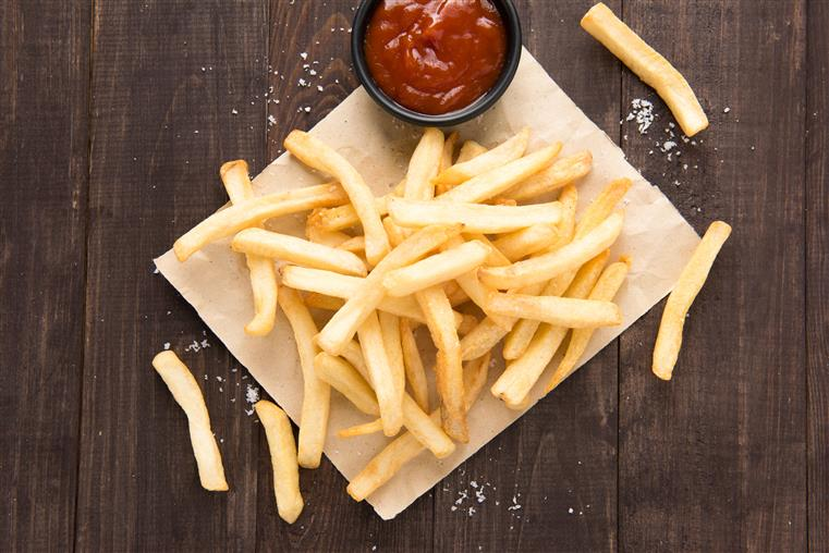 stack of french fries with ketchup on a wooden table