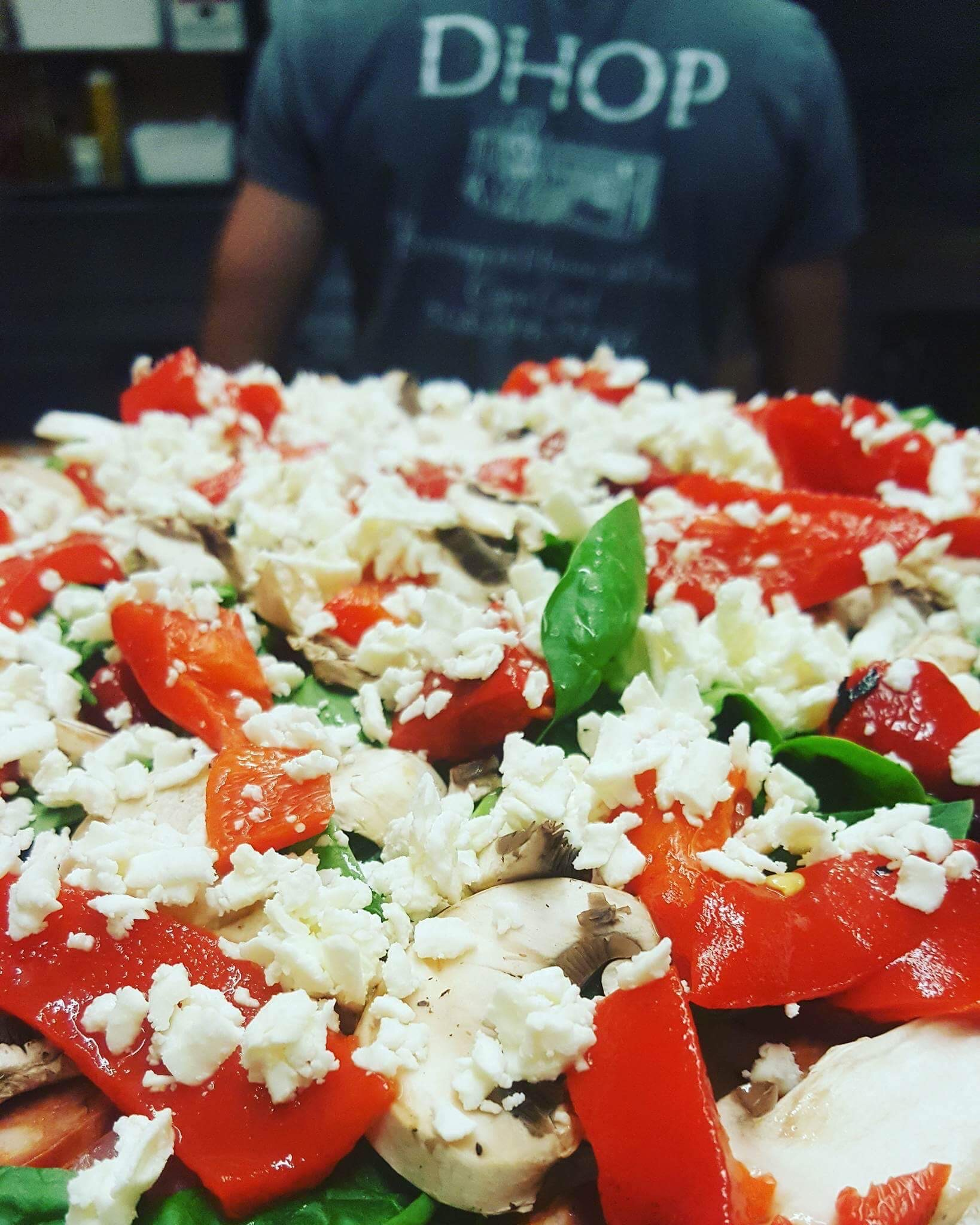 large pizza topped with feta cheese, tomatoes, basil leaves and mushrooms