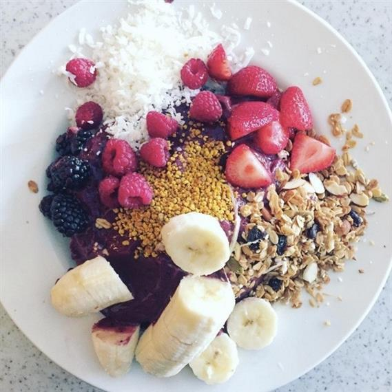 White dish with granola, almonds, bananas, strawberries, raspberries, blackberries, shredded coconut.