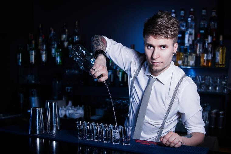 Bartender pouring alcohol into shot glasses behind the bar