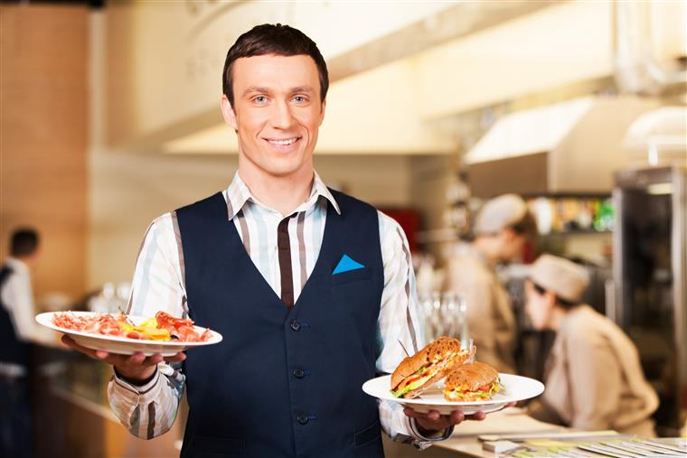 waiter smiling holding two plates of food