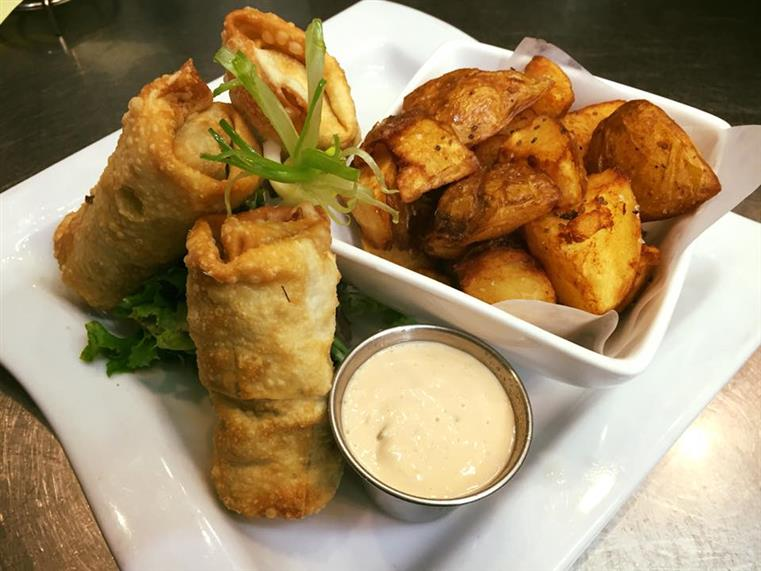 Fried rolls with dipping sauce and side of potatoes