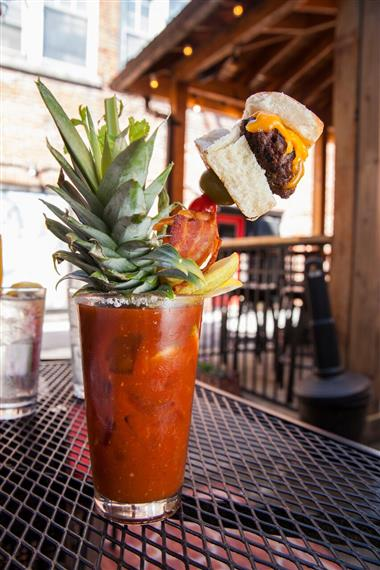 bloody mary with the top of a pineapple as a garnish also with a cheeseburger, bacon, olives and celery on a stick