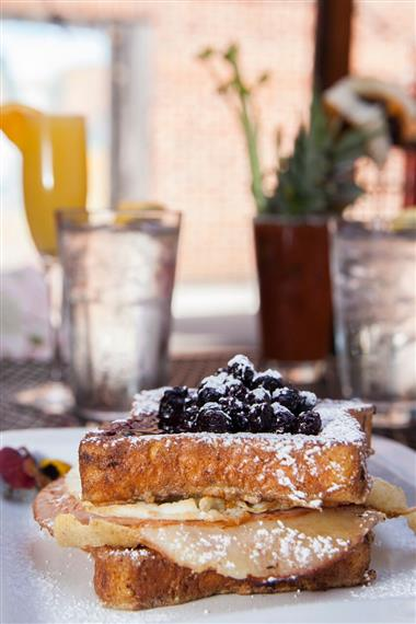 monte cristo with cheese, turkey, and powdered sugar topped with blueberries