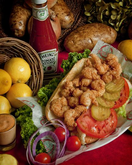 popcorn shrimp poboy with tomatoes, pickles and lettuce