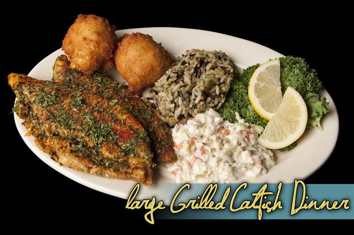 large grilled catfish dinner with rice and hush puppies