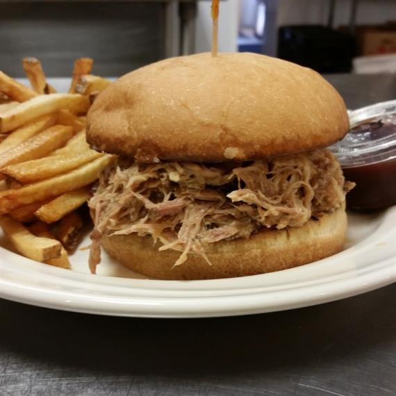 pulled pork sandwich on plate with side of french fries and barbecue sauce