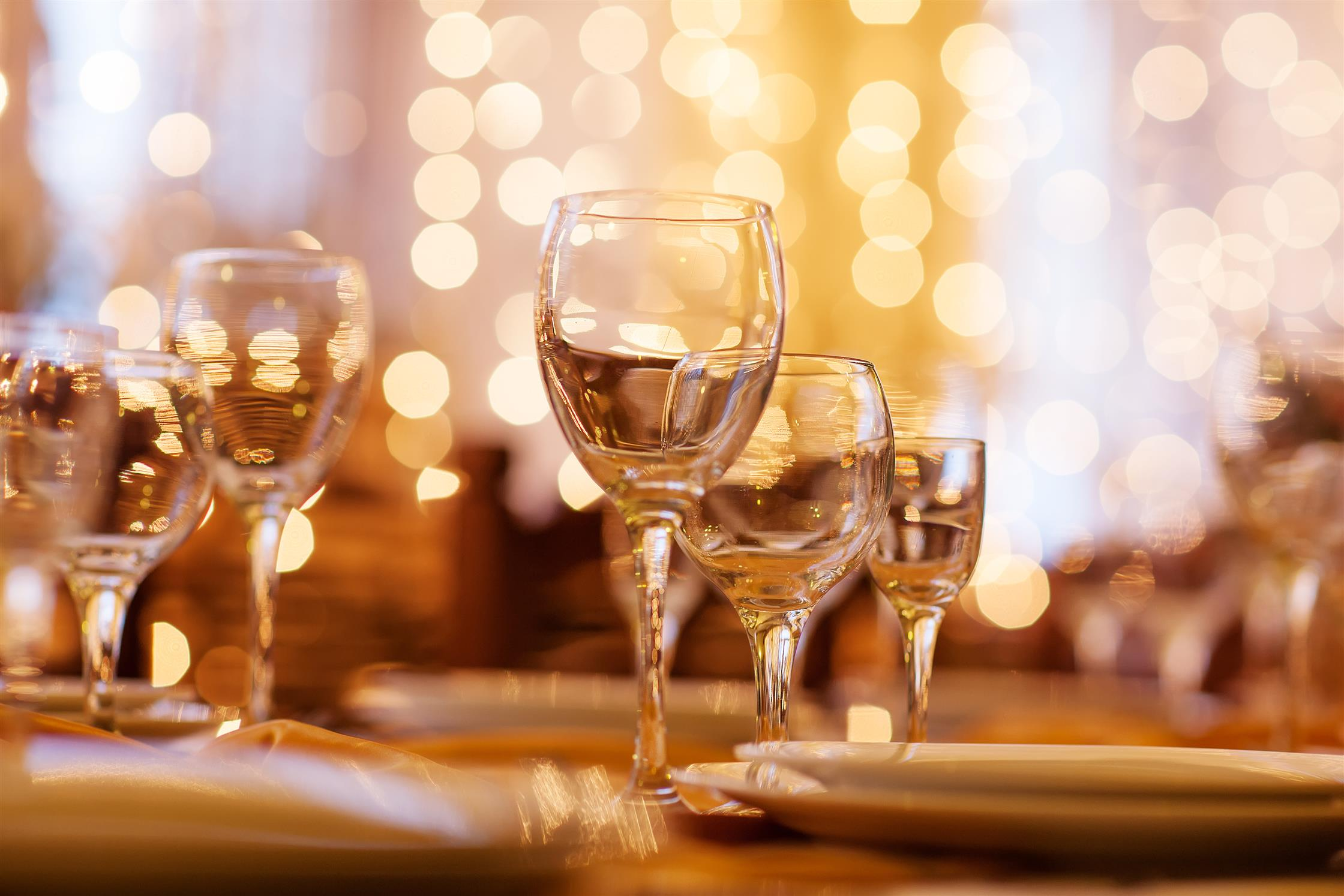 Wine glasses and dish on table with golden lighting