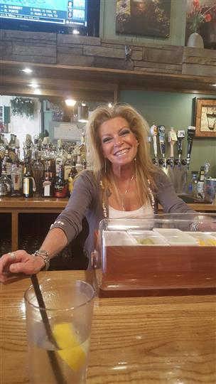 A woman smiling posing for a photo behind the bar