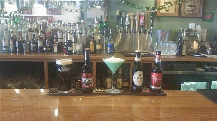 A glass of Guinness beer, a glass of a cocktail, and three bottles of beer at the bar