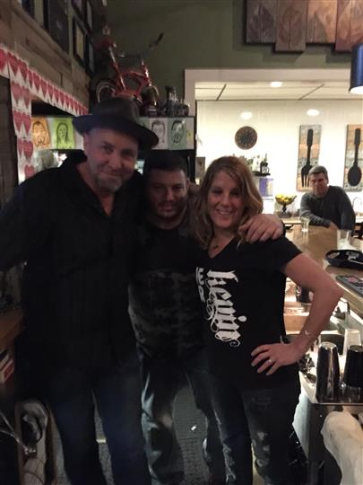 Two men and a woman posing for a photo behind the bar