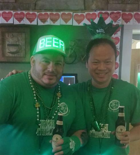 Two men with green t-shirts and green huts holding a beer posing for a photo in the Rock Garden Cafe