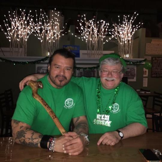 Two men eith green t-shirts posing for a photo in the Rock Garden Cafe