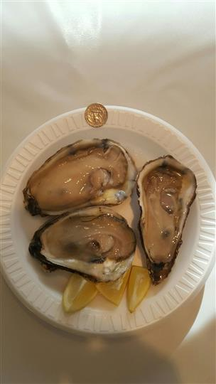 Three raw oysters on the half shell served with lemon