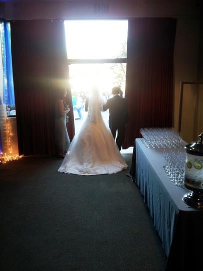 bride walking outside for her wedding with her father