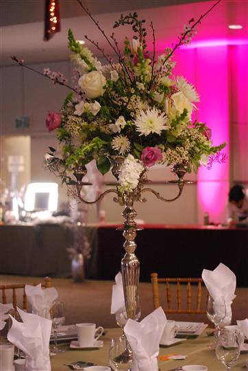 centerpiece with flowers in a silver tall vase
