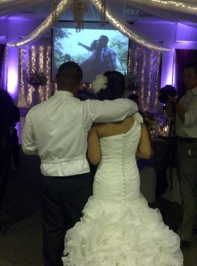 backshot of the bride and groom looking at a slideshow