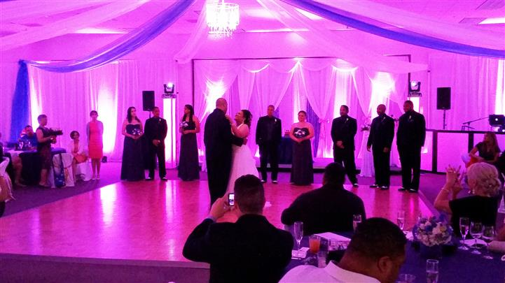 bride and groom dancing under the pink lights