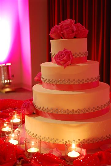 white cake with pink bows and roses on it