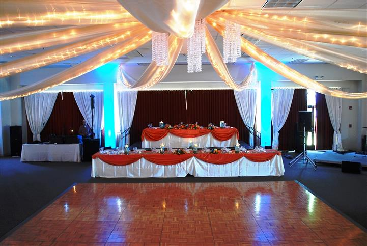 inside area with the dance floor and table set up with red accents